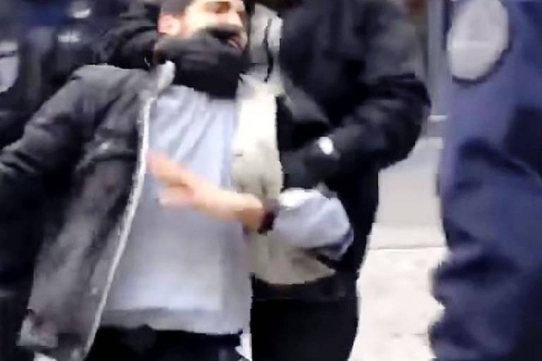 """In this video grab taken on July 19, 2018 from footage filmed on May 1, 2018 shows a man identified as Elysee Chief Security Officer Alexandre Benalla wearing a police visor as he drags away a demonstrator during May 1 protests in Paris. One of President Emmanuel Macron's top security officers was at the centre of a potentially damaging scandal for the French leader on July 19, 2018 after being filmed hitting a protester.Le Monde newspaper published a video showing Alexandre Benalla striking and then stamping on a young man while wearing a police visor during a demonstration in central Paris on May 1. / AFP PHOTO / Tahar Bouhafs / Tahar Bouhafs / RESTRICTED TO EDITORIAL USE - MANDATORY CREDIT """"AFP PHOTO / Tahar Bouhafs """" - NO MARKETING NO ADVERTISING CAMPAIGNS - DISTRIBUTED AS A SERVICE TO CLIENTS == NO ARCHIVE"""