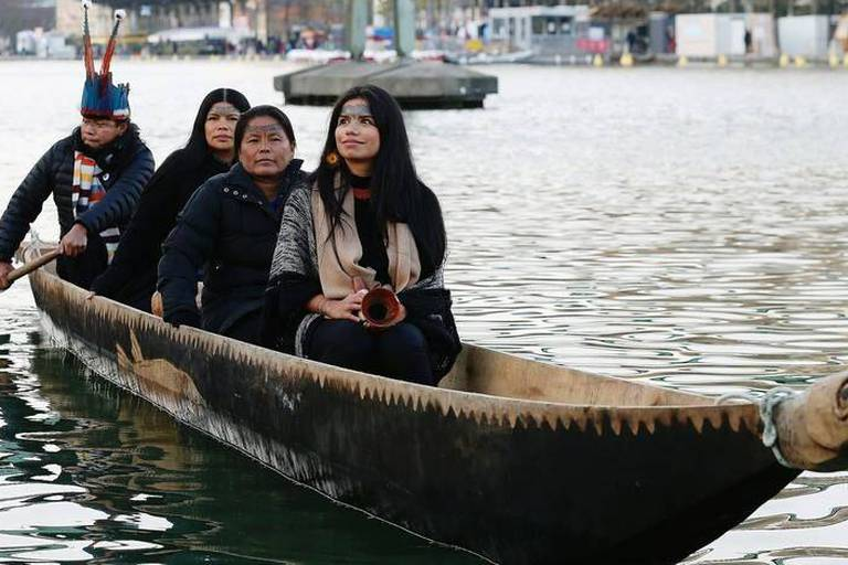 """Members of the Sarayaku indigenous community ride the """"Canoe of Life"""" along the Bassin de la Villette in Paris on December 8, 2015 during the COP21 climate change conference. / AFP / THOMAS SAMSON"""