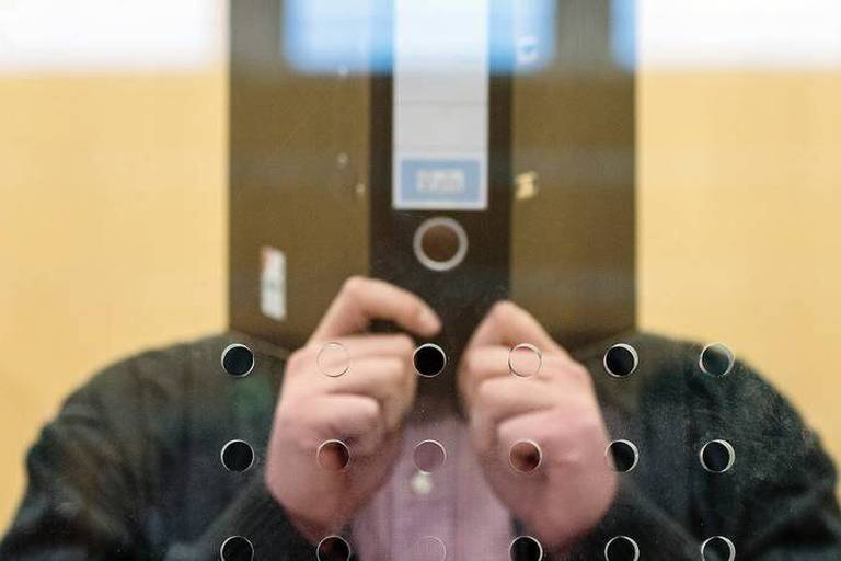 The defendant Nils D. stands with a file folder covering his face in the courtroom in Duesseldorf, Germany, 20 January 2016. The suspected terrorist with the 'Islamic State' (IS) must stand trial in the higher regional court. The 25 year old from Dinslaken allegedly belonged to an IS special unit in Syria that tracked down deserters and dissenters. Photo: FEDERICO GAMBARINI/dpa Reporters / DPA