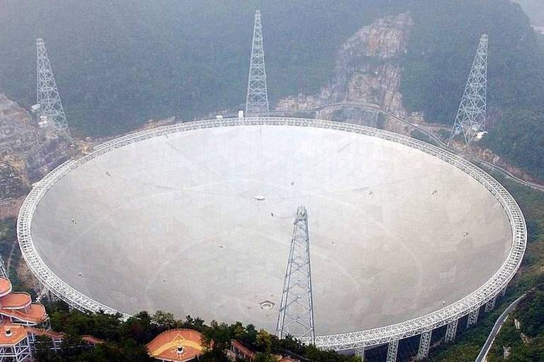 An aerial view shows the Five-hundred-meter Aperture Spherical Telescope (FAST) in the remote Pingtang county in southwest China's Guizhou province, Sunday, Sept. 25, 2016. The world's largest radio telescope began searching for signals from stars and galaxies and, perhaps, extraterrestrial life Sunday in a project demonstrating China's rising ambitions in space and its pursuit of international scientific prestige. (Chinatopix via AP)