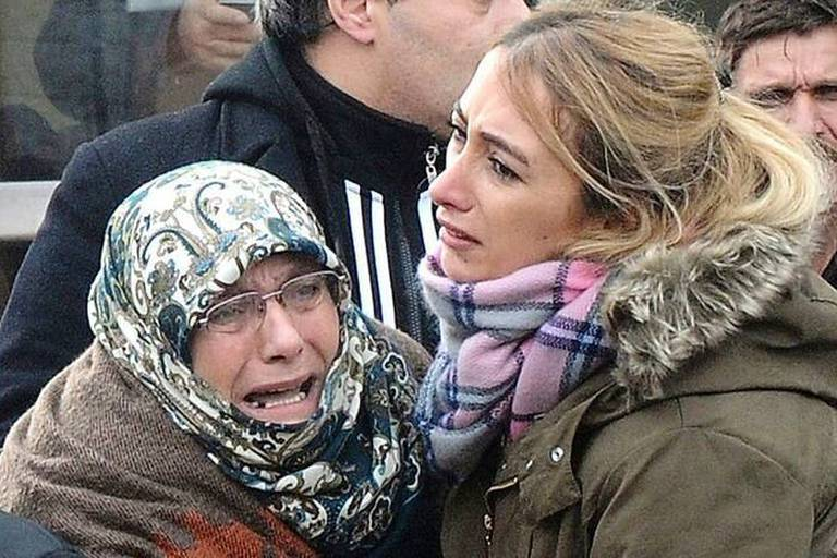 Family members of victims of an attack on a crowded Istanbul nightclub mourn outside the morgue in Istanbul, Sunday, Jan. 1, 2017. An assailant believed to have been dressed in a Santa Claus costume and armed with a long-barrelled weapon, opened fire at a nightclub in Istanbul's Ortakoy district during New Year's celebrations, killing dozens of people and wounding dozens of others in what the province's governor described as a terror attack.(DHA-Depo Photos via AP)