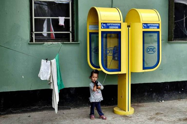 TOPSHOT - A girl plays with the handset of a phone booth at the refugee camp of Schisto on June 8, 2016. The Schisto camp, which accomodates some 1,700 migrants of all ages, the vast majority of them from Afghanistan, is an open facility where people who are assigned there are free to come and go. / AFP PHOTO / ARIS MESSINIS