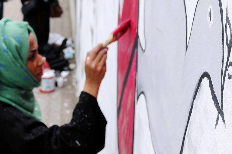 """(180412) -- SANAA, April 12, 2018 () -- An artist draws a piece of graffiti artwork during a graffiti campaign named """"All We Wish Is Peace, Silent Victims"""" in Sanaa, Yemen, on April 12, 2018. Yemeni activists held a graffiti campaign to chart the suffering of women and children in the war. (/Mohammed Mohammed) Reporters / Photoshot"""