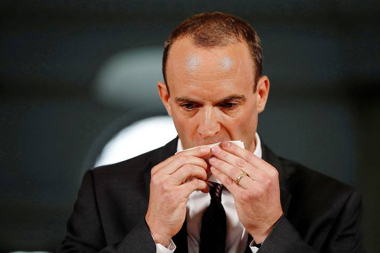 Britain's Secretary of State for Exiting the European Union (Brexit Minister) Dominic Raab wipes his face as he delivers his speech outlining the government's plans for a no-deal Brexit, in central London on August 23, 2018. (Photo by PETER NICHOLLS / POOL / AFP)