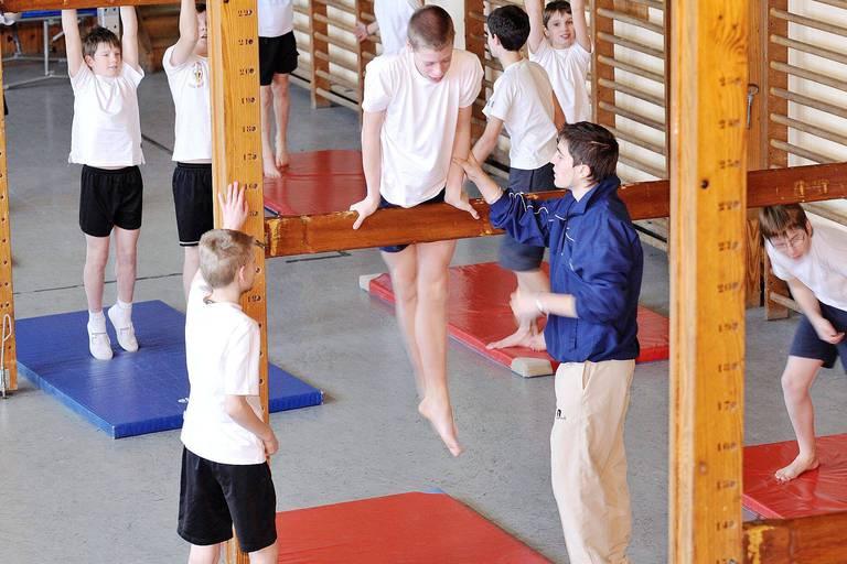 Enseignement secondaire : les étudiants au cours de gymnastique avec leur professeur.