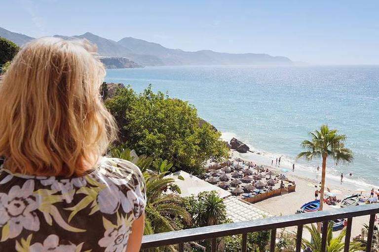 A Woman Looks Out Over A Balcony At Calahonda Beach; Nerja, Malaga Province, Andalusia, Spain Reporters / Design Pics
