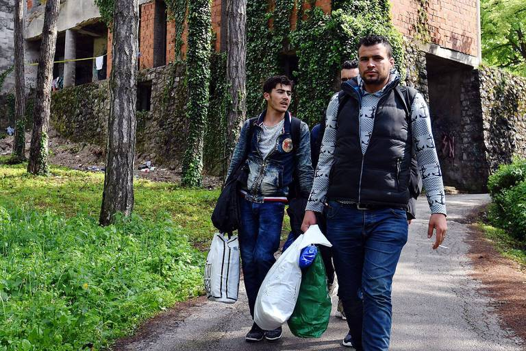 """Migrants walk outside an abandoned building in the main park of the North-Western Bosnia town of Velika Kladusa on May 10, 2018. The building is being refitted with infrastructure to accept African-Asian migrants who make their stop in Bihac, where they rest before continuing """"the final Bosnian leg"""" on their journey towards Velika Kladusa, a Bosnian town at the Bosnia - Croatia border. Until recently, Bosnia and its mountainous terrain were avoided by migrants travelling from northern Africa, Middle East or Asia, who, despite the closure of EU borders in March 2016, continued to pass through the Balkans. But, since late 2017 Bosnia is facing the passage of hundreds of migrants, becoming a leg of a new """"Balkans route."""" / AFP PHOTO / ELVIS BARUKCIC"""