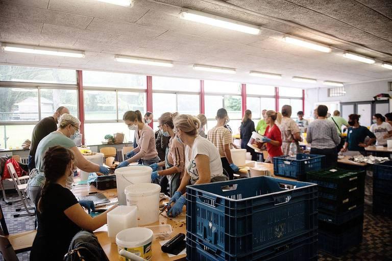 Les bénévoles préparent les repas en groupe, dans le réfectoire.