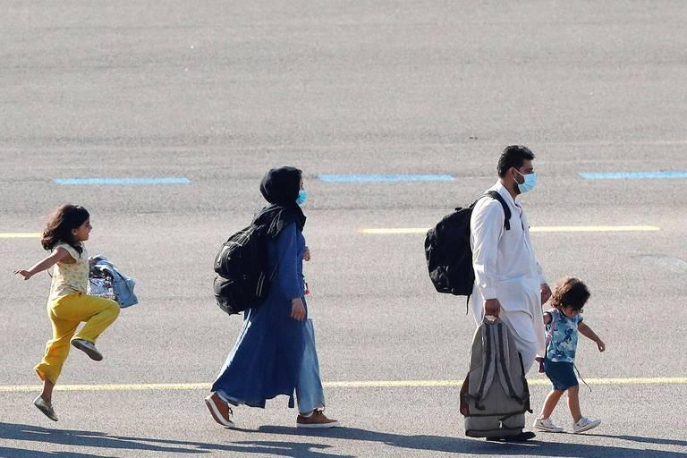 Le 25 août 2021, des personnes évacuées d'Afghanistan arrivent à l'aéroport militaire de Melsbroek, en Belgique, après l'entrée des insurgés talibans dans la capitale afghane.