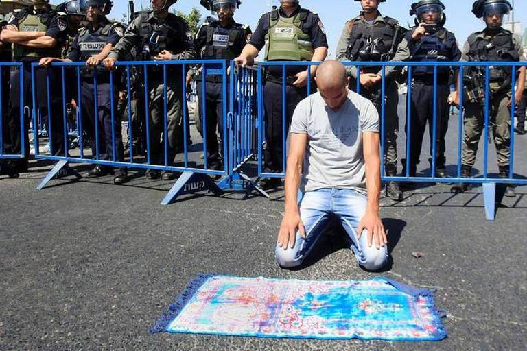 Image #: 39475450 A Palestinian Muslim worshipper, under the age of 40 years old, performs the traditional Friday prayers on a street as Israeli police blocks the access to Al-Aqsa Mosque, outside the Old City walls in East Jerusalem on September 18, 2015. Israel deployed hundreds of extra police around the Old City of Jerusalem on Friday to bar young Muslim men from prayers at the Al-Aqsa mosque site after Palestinian leaders called for a 'day of rage' to protest at new Israeli security measures. Photo by Mahfouz Abu Turk APA /Landov Reporters / Landov