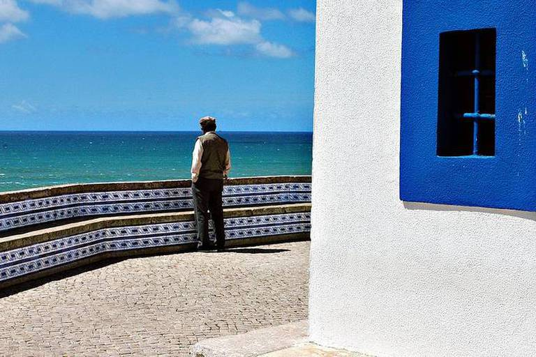 Man watching the sea in the village of Ericeira in the region of Algarve in Southern Portugal. Tourism, village Reporters / Andia *** Local Caption ***