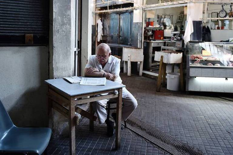 A man reads a newspaper outside a shop in the main meat market of the northern Greek port city of Thessaloniki, Tuesday, Aug. 11, 2015. Greece has agreed on the broad terms of a new three-year bailout package with international creditors, with only a few details left to iron out, the finance minister said Tuesday.(AP Photo/Giannis Papanikos)